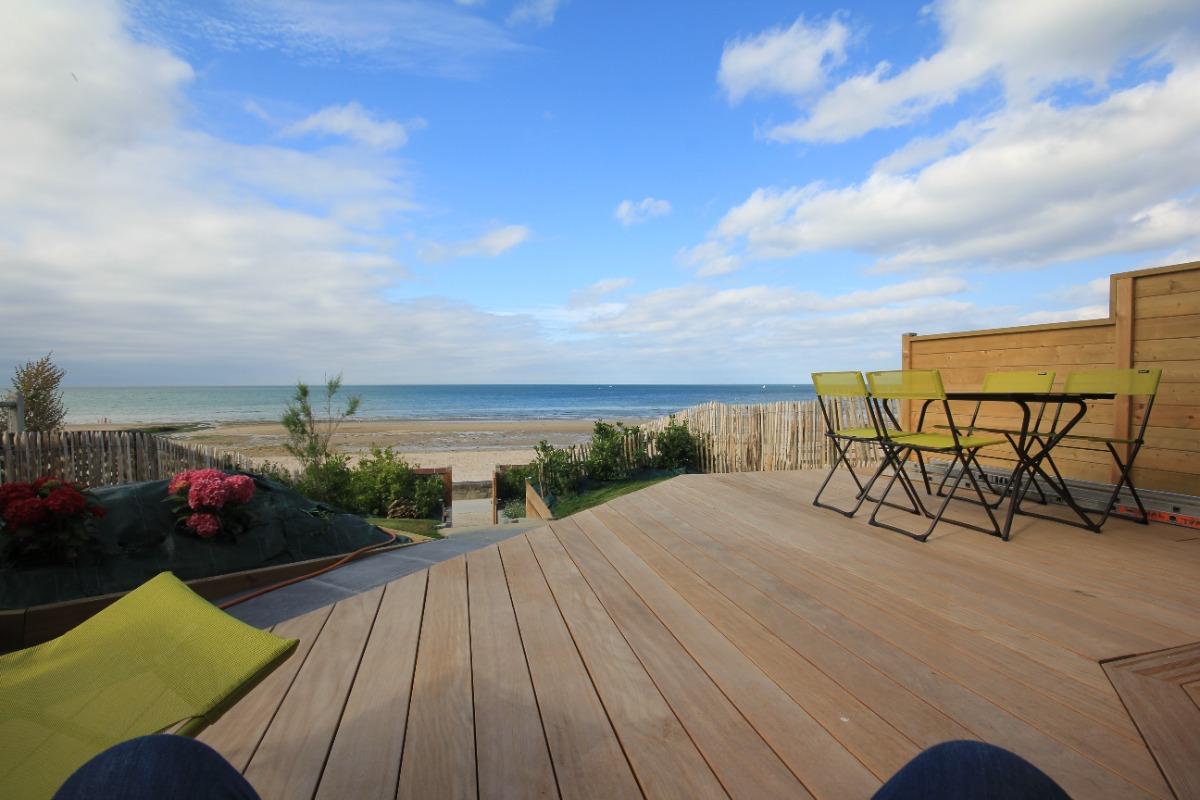 dos à la maison, sur la terrasse principale, quelques marche au milieu du jardin et passé le portillon c'est la digue haute/promenade. - Location de vacances - Langrune-sur-Mer