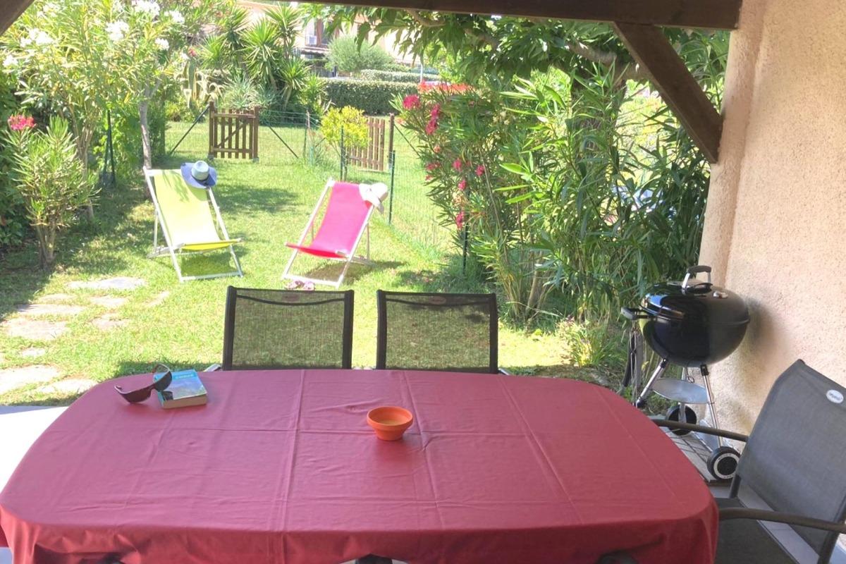 Le jardin devant la terrasse couverte, avec transats et barbecue pour farniente et grillades. - Location de vacances - Poggio-Mezzana