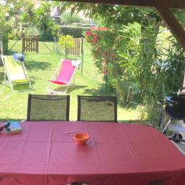 Le jardin devant la terrasse couverte, avec transats et barbecue pour farniente et grillades. - Location de vacances -
