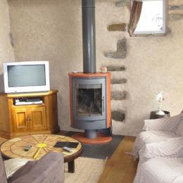 salon avec poêle à bois et canapé convertible 2 places - Location de vacances - Kergloff