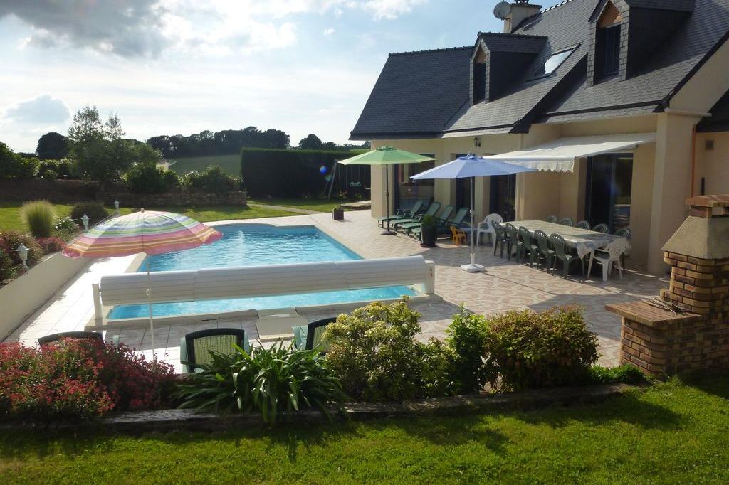 Vue d'ensemble extérieure avec salon de jardin, terrasse et piscine - Location de vacances - Saint-Yvi