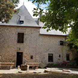 La terrasse avec mobilier de jardin et la roue de pressoir en granit - Location de vacances - Saint-Malo