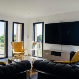 La Villa Touesse - L'espace-salon avec installation Home cinéma et la jolie vue sur la compagne environnante - Location de vacances - Saint-Coulomb
