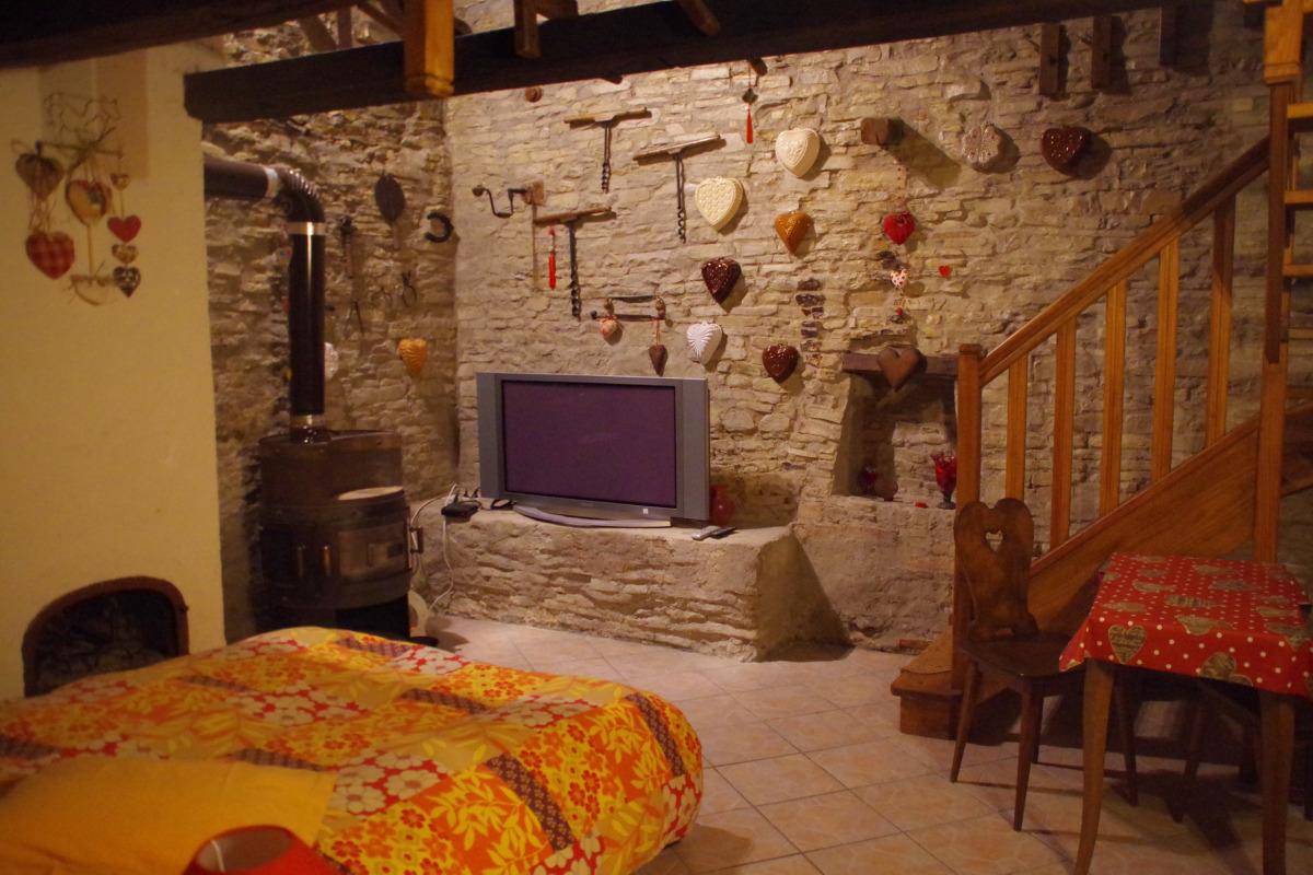 La partie plain-pied accueille un grand lit et un coin salon, équipé d'un téléviseur grand écran plat, au coin du poêle à bois. - Chambre d'hôtes - Racrange