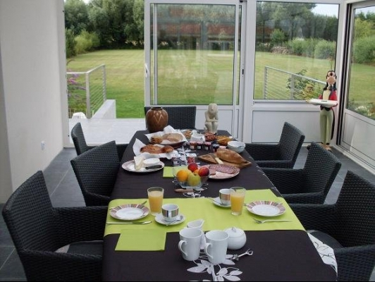 petit déjeuner dans la véranda avec vue sur le jardin et les pics-vert - Chambre d'hôtes - Rang-du-Fliers