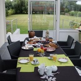 petit déjeuner dans la véranda avec vue sur le jardin et les pics-vert - Chambre d'hôte - Rang-du-Fliers
