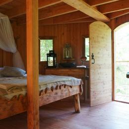 le 1er niveau : grand lit double, terrasse et espace de vie - Chambre d'hôtes - La Tour-d'Auvergne