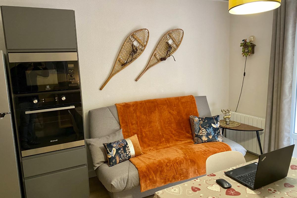 Coin salon avec canapé table basse et éclairage indirect - Location de vacances - Cauterets