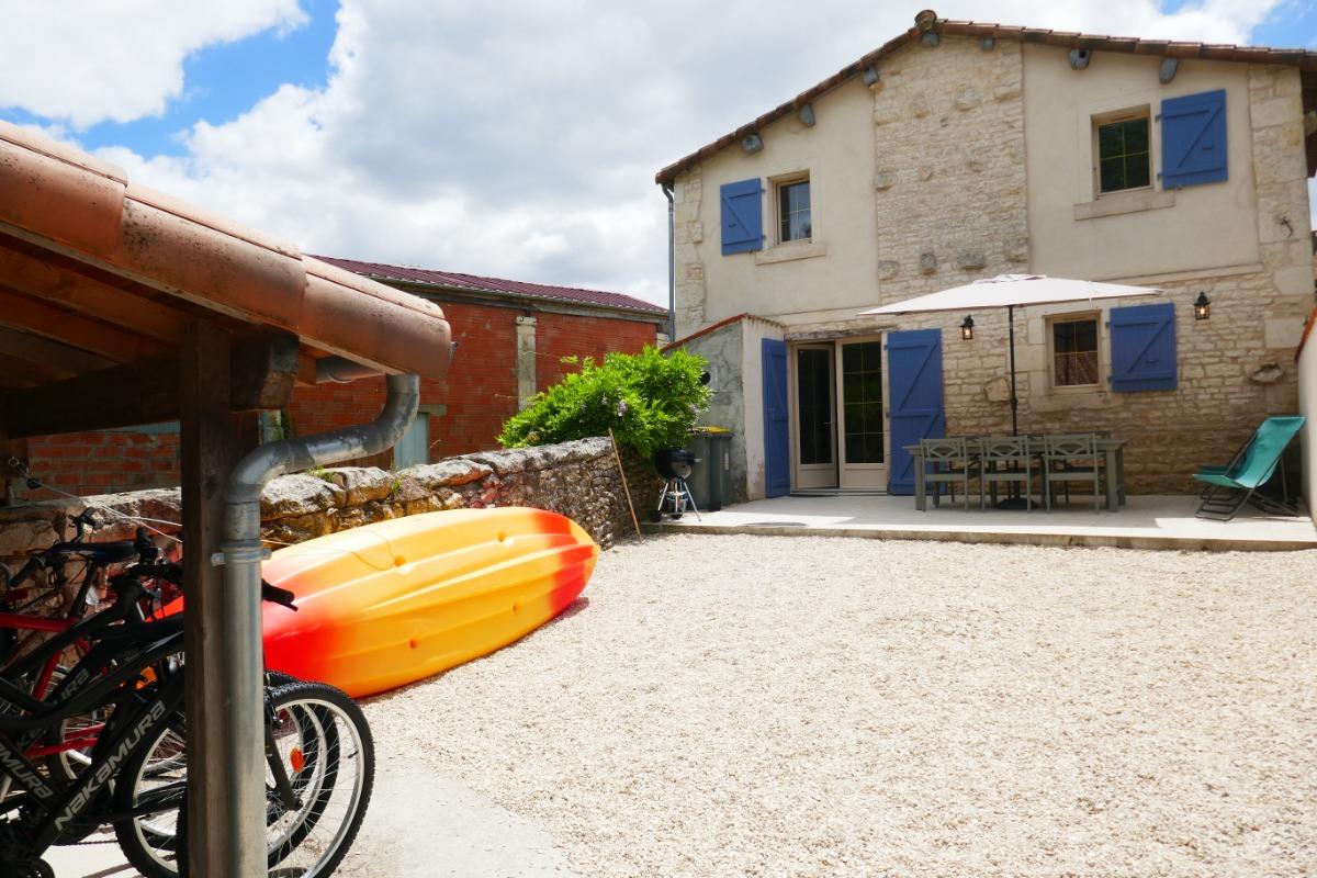 Façade de la maison, terrasse privative attenante. Table d'extérieur, transats, canoës et vélos vous attendent pour partager des moments en famille inoubliables. Partez à l'assaut du Marais poitevin ! - Location de vacances - Le Vanneau-Irleau