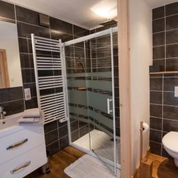 La salle d'eau privative de la suite est déclinée en blanc, bois et ardoise est équipée d'une vaste douche à l'italienne, d'une douche de pluie, d'un lavabo double vasques et de toilettes privatifs. - Location de vacances - Xonrupt-Longemer
