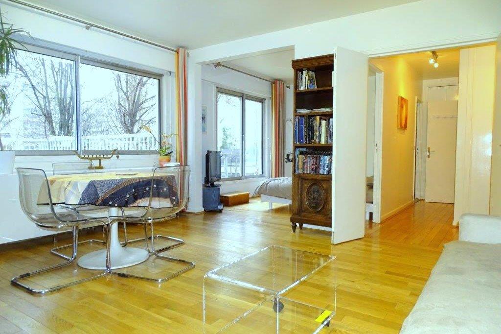 Un vaste séjour, confortablement équipé, éclairé par une large baie vitrée donnant sur le parc - Location de vacances - Courbevoie / Paris La Défense